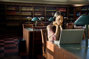 A young woman uses a white laptop in the library