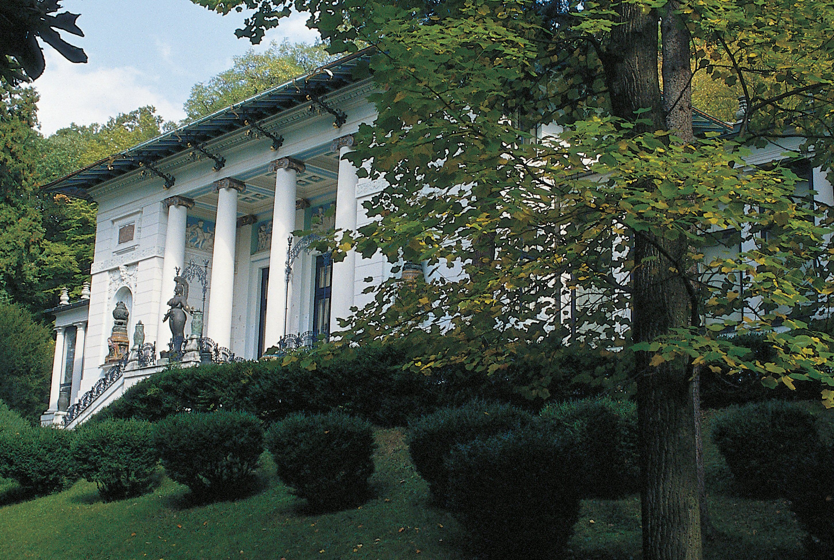 columned white building in wooded landscape
