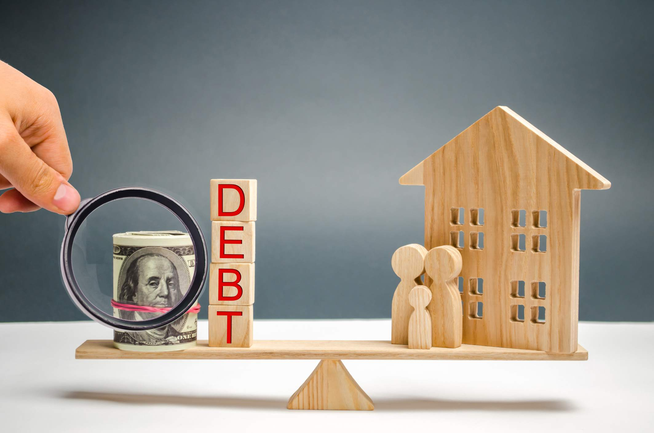 Blocks with the word debt and money, family and wooden house