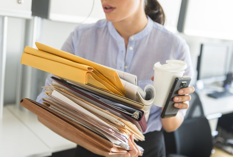 A close-up image of a woman balancing a large stack of papers and folders. In one hand, she holds a coffee cup and cell phone.