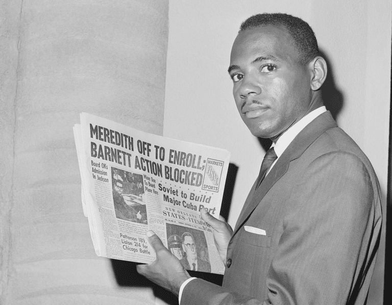 James Meredith, the first African American student to enroll at the University of Mississippi, holds a newspaper as he attempts to register at the university.