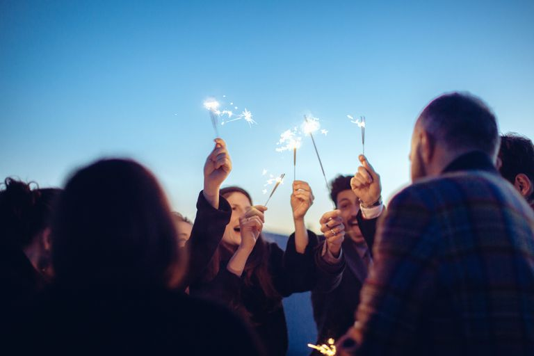 New year greetings and quotes group of friends holding sparklers in air at party m4hsunfo