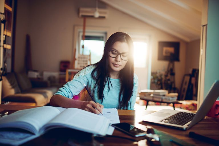 Student working at home with laptop and school books.