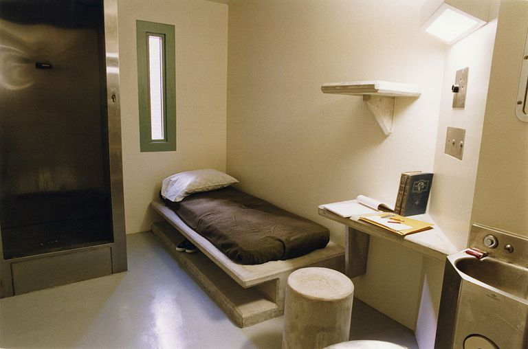 A bed, desk, and sink in prisoner's cell