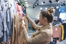 woman looking at price tag while shopping