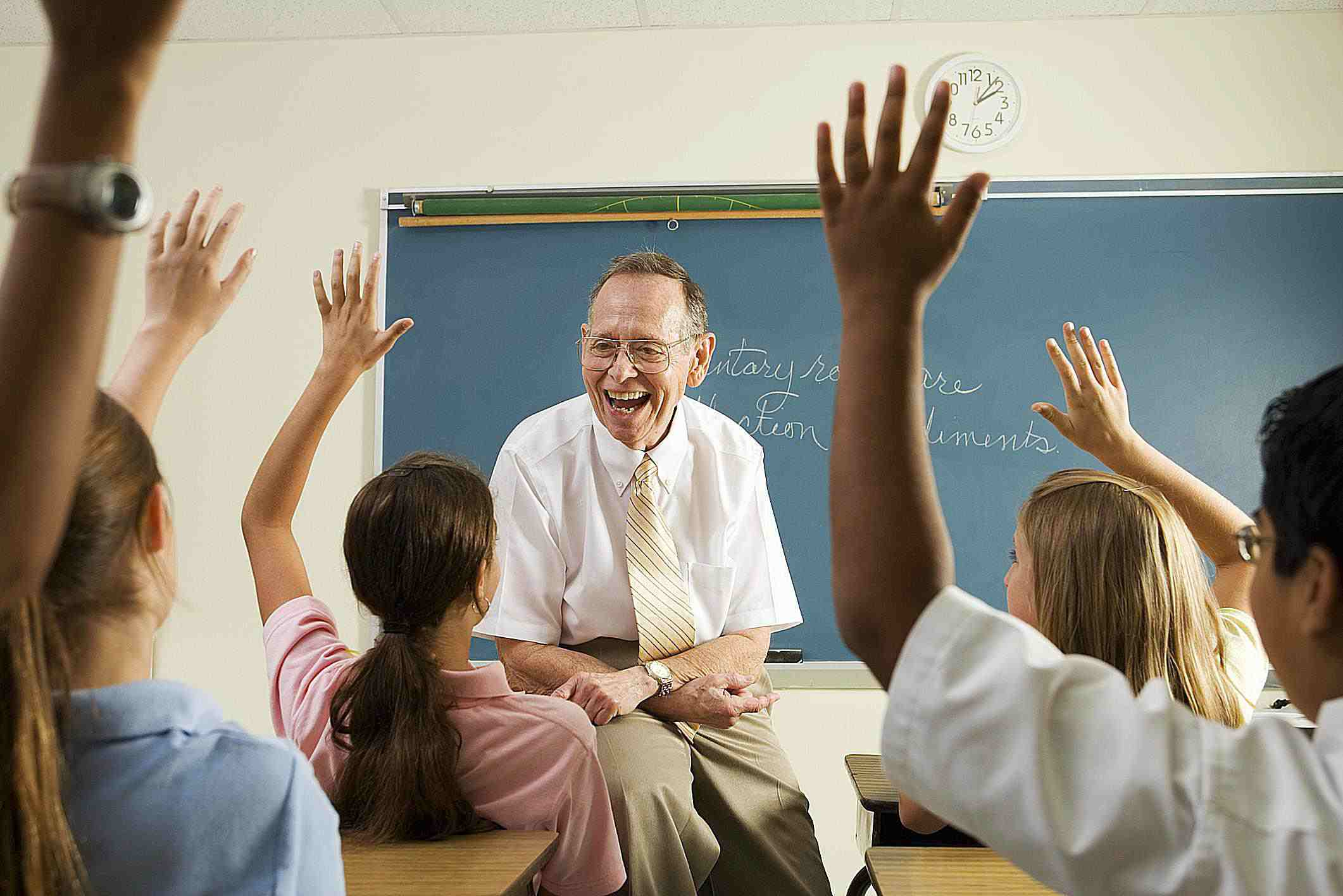 students with raised hands and teacher sitting on desk