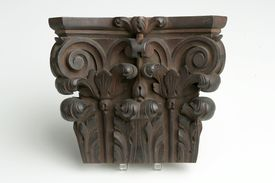 wooden sculpting with flat top, swirl volutes on each side, and leafy ornamentation on the surface