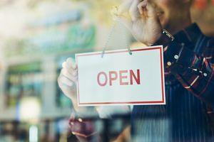 Varón colocando cartel de abierto en un negocio