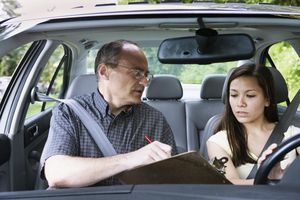 Teenage girl sitting in car with driving instructor