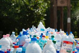 Lots of plastic bottles outside with trees obscured in background.