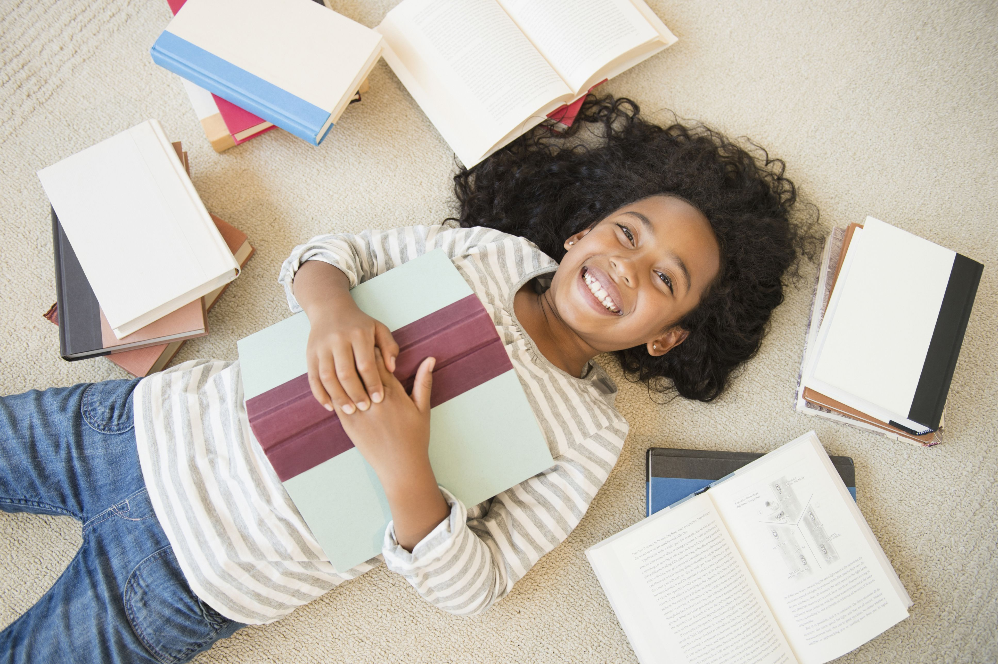 A girl laying on the floor surrounded by books.