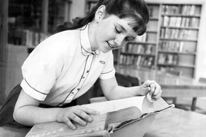 Vintage photo of young girl looking through a well-used dictionary