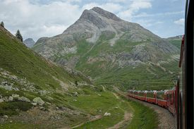 climactic order: Train winds through mountain landscape