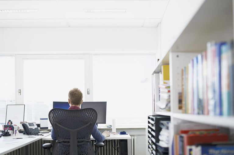 Business man sitting infront of computer, backview