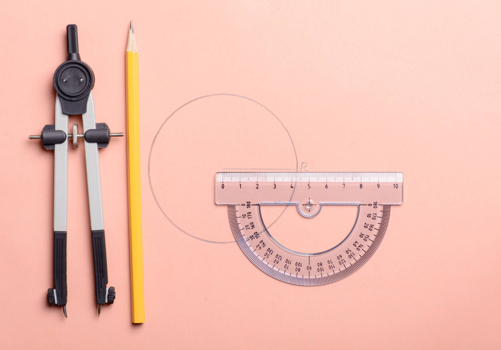 Two types of protractor with a pencil on a piece of paper.