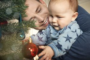 Father and baby looking at christmas tree