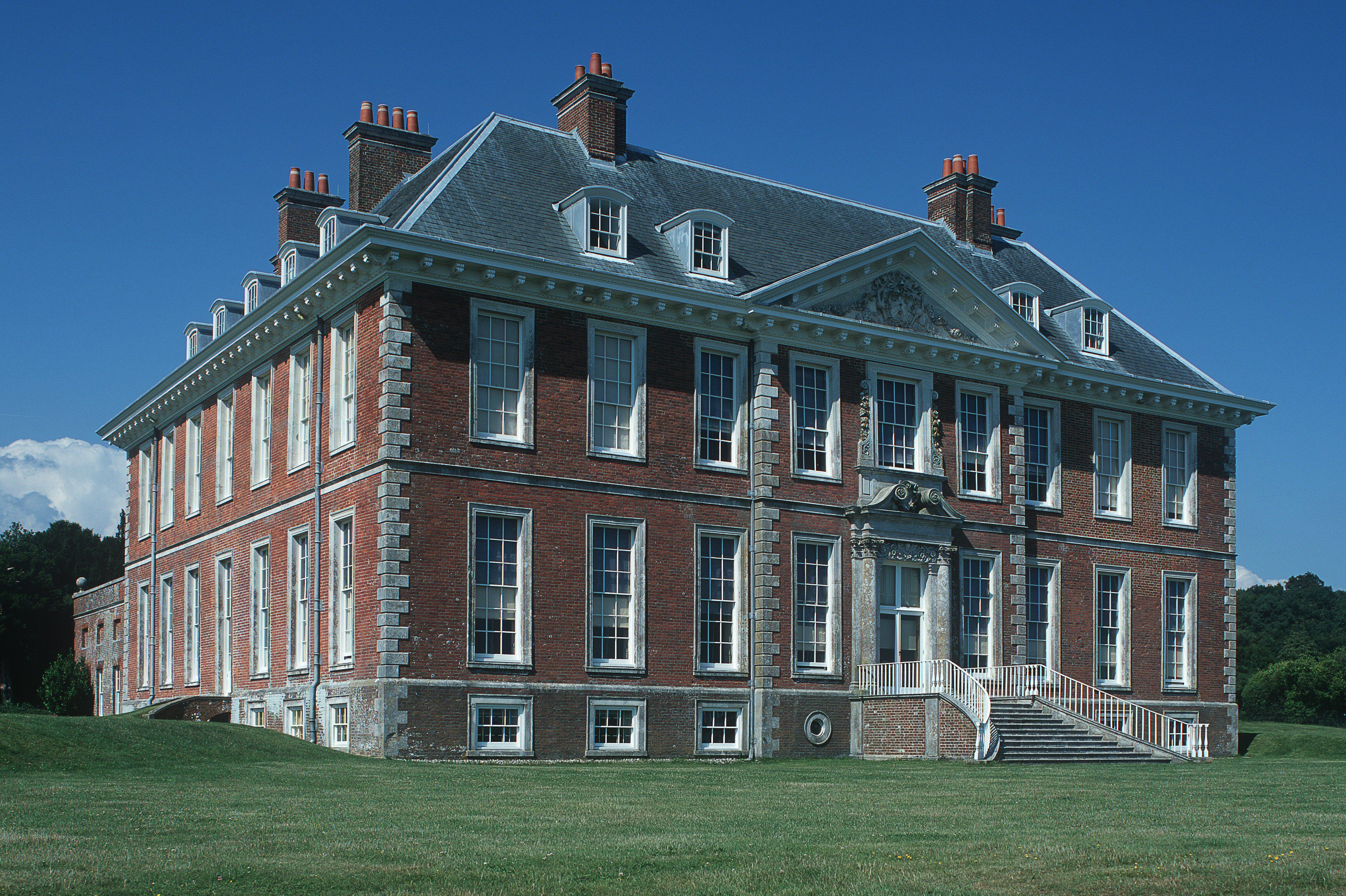 Accentuated corners or quoins on a 17th century brick mansion in England, dormers, front pediment