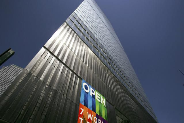 Photo of skyscraper with colorful banner pronouncing 7 World Trade Center OPEN.
