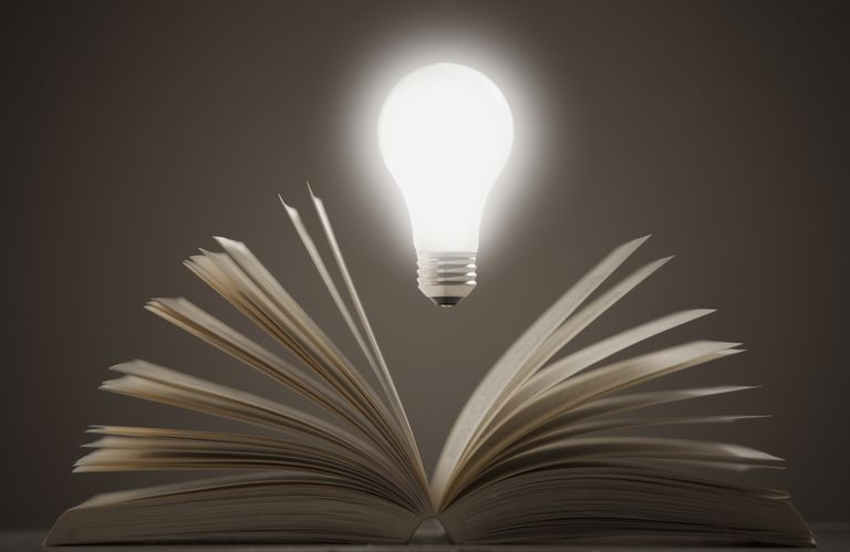 Light bulb floating above open book.