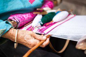 Close up of hand of old woman weaving.