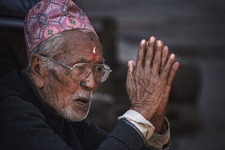 Close up of elder man giving namaste greeting.