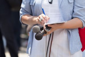 Midsection Of Journalist Holding Microphones While Writing On Note Pad
