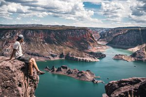 man sitting on high rock overlooking canyon