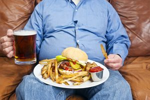 Obese man eating junk food