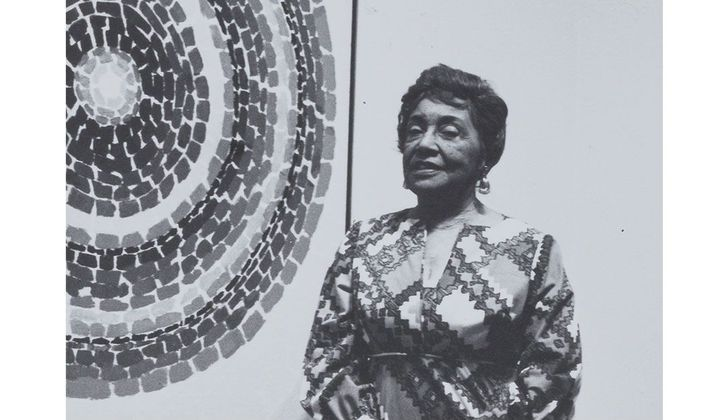 black and white image of Alma Thomas in front of one of her circle abstractions
