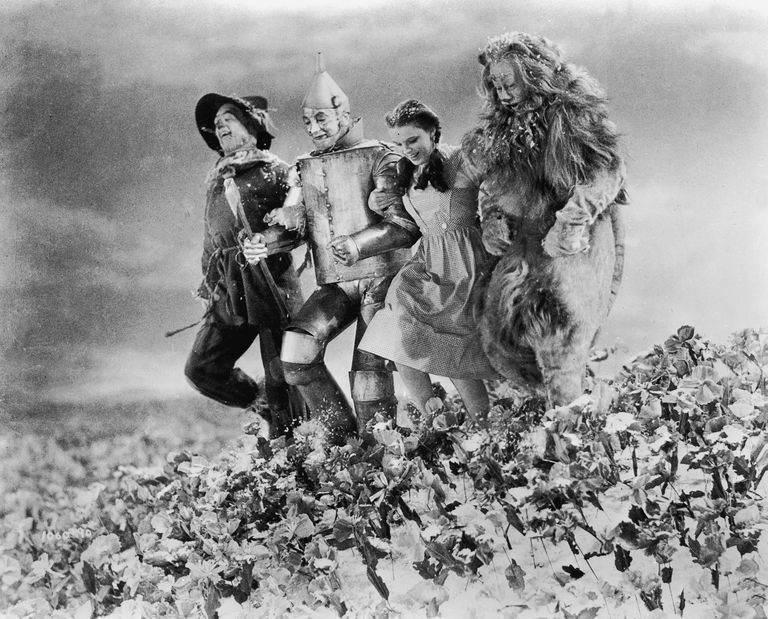 The Scarecrow, Tin Man, Dorothy, and the Cowardly Lion skipping in the Wizard of Oz.