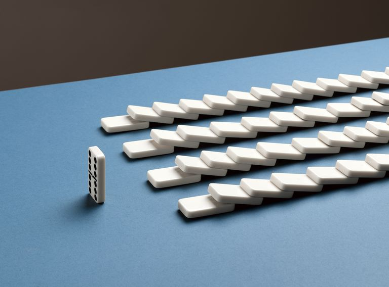 Several rows of dominos have been toppled and one domino is still upright.