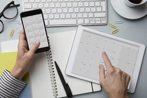woman holding smartphone and tablet with calendar on desk