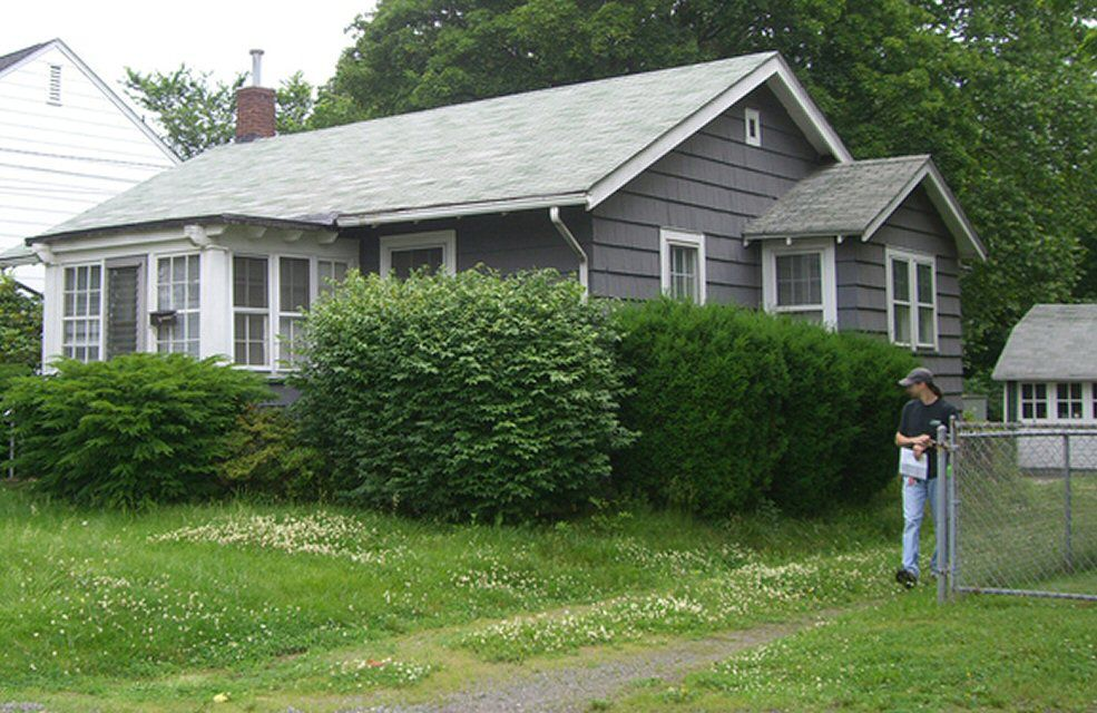 Grey Shake Shingle Cottage With A Green Roof