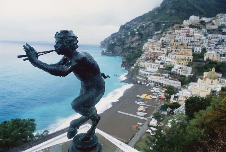 Bronze Of Pan Above Town With Ocean