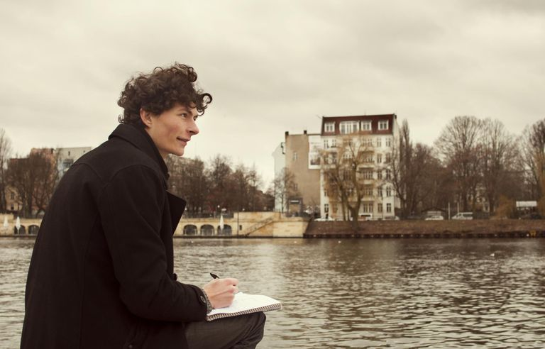 Man Writing in Journal by River in Berlin