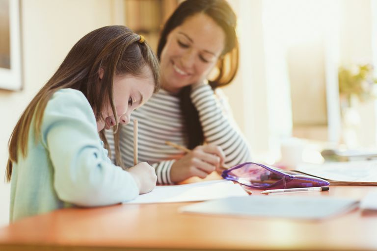 Mom working with daughter on school work at home