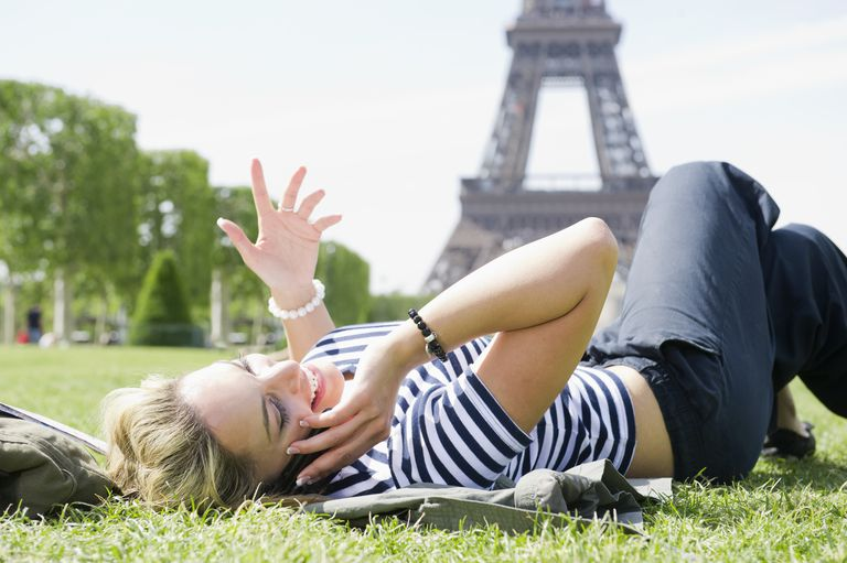 Hispanic woman using cell phone in park near Eiffel Tower