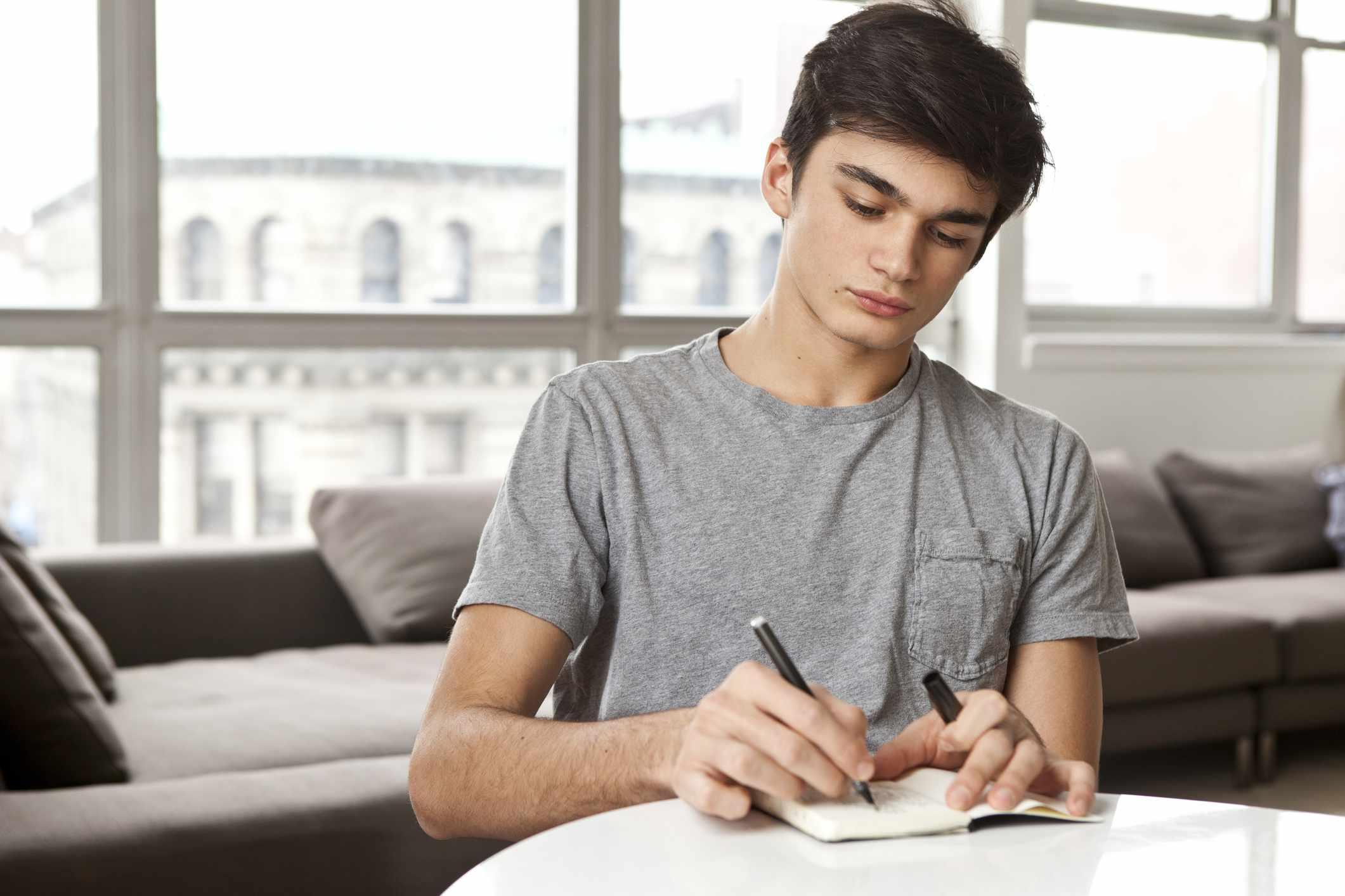 Teenager writing at home