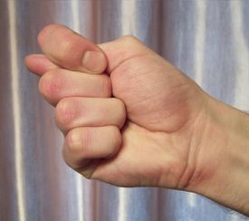 Person holding thumb between middle and forefinger.