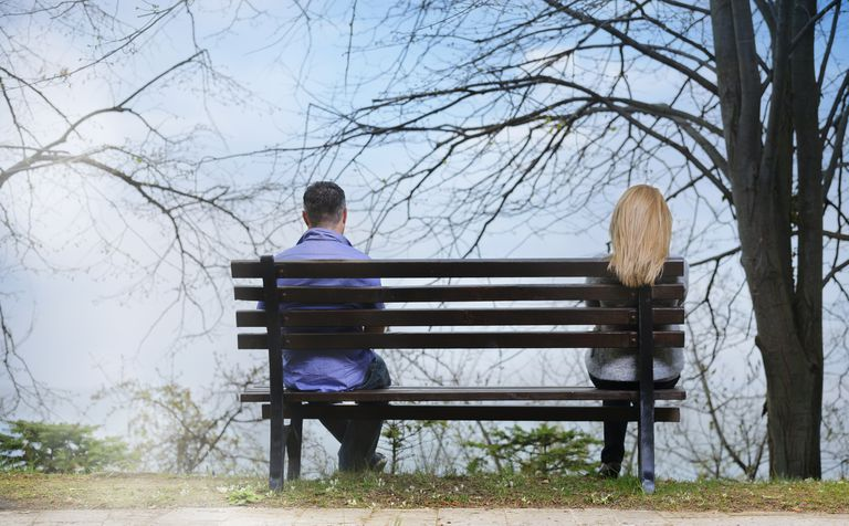 A man and woman are seated at opposite ends of a park bench, facing away from the camera.