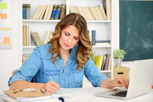 Teacher writing at her desk