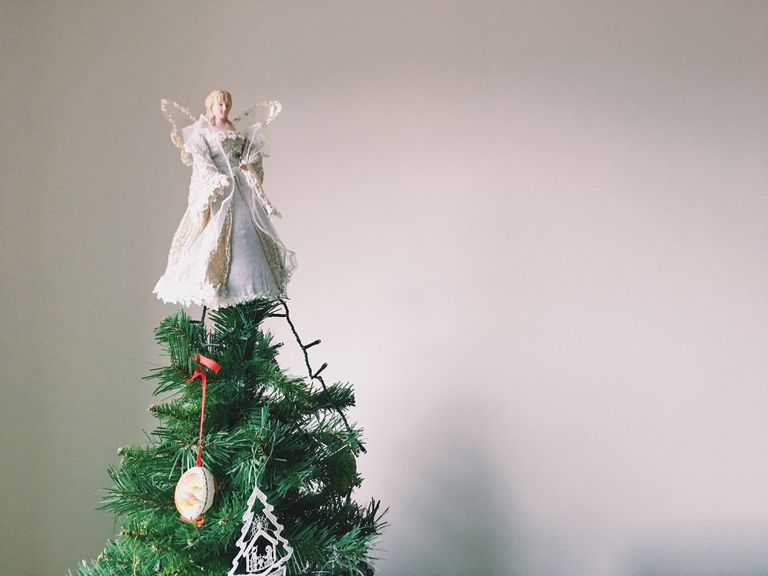 Angel On Christmas Tree Top Against Wall