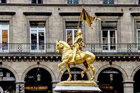 Golden statue of Joan of Arc on a horse holding a flag.