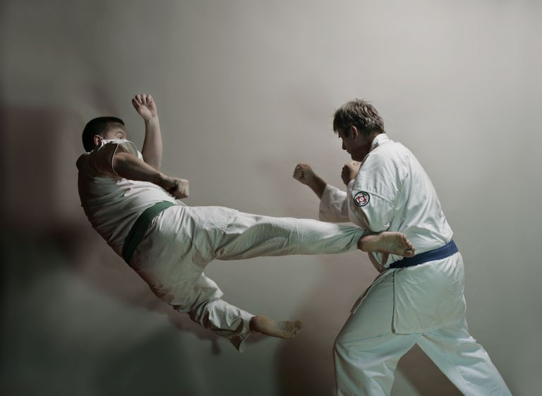 2 men practicing karate kicks