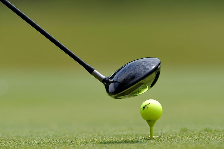 A golf driver poised by the ball