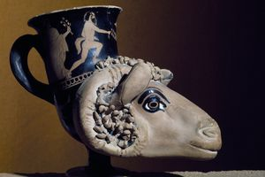 Red figure pottery of ram's head rhyton with maenads and dancing satyrs.