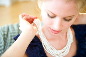 Woman puts on a fancy pearl necklace