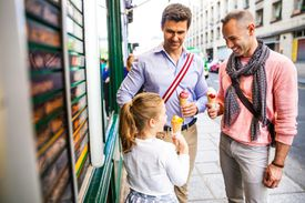 Fathers enjoying ice cream with daughter
