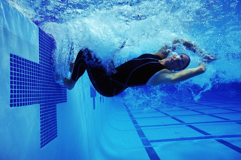 Under water view of female swimmer performing turn in competition.
