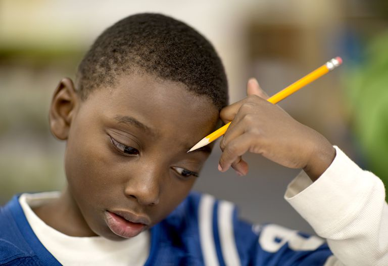 Fourth grade boy works on a math problem.